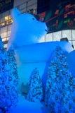 大熊雕象和光装饰美丽的圣诞树 免版税库存照片