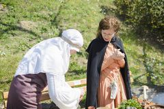 大特尔诺沃,保加利亚, 2015年4月04日,两有葡萄酒衣裳的妇女烹调在中世纪市场的中世纪膳食 库存图片