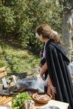 大特尔诺沃,保加利亚, 2015年4月04日,有葡萄酒衣裳的妇女烹调在中世纪市场的中世纪膳食 免版税图库摄影