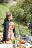 大特尔诺沃,保加利亚, 2015年4月04日,有葡萄酒衣裳的妇女烹调在中世纪市场的中世纪膳食 免版税库存图片