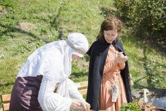 大特尔诺沃,保加利亚, 2015年4月04日,两有葡萄酒衣裳的妇女烹调在中世纪市场的中世纪膳食在强的tsarevets 免版税库存照片