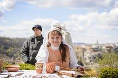 大特尔诺沃,保加利亚, 2015年4月04日,俏丽的女孩展示如何编织与柳条的一个篮子在大特尔诺沃市场,她 免版税库存照片