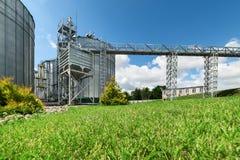 大现代粮仓 在前景有一棵色情绿色草坪草 库存照片