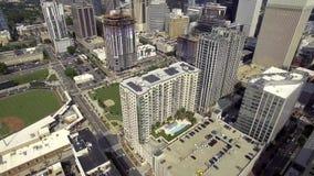 大现代都市繁忙的城市高摩天大楼建筑学和绿色棒球场4k空中寄生虫射击的 影视素材