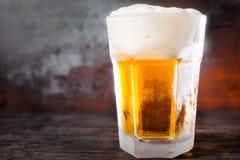 大玻璃用低度黄啤酒和泡沫一个大头在老黑暗的 库存图片