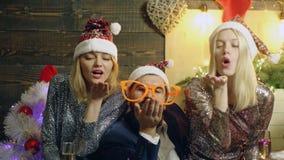 大玻璃的有胡子的人和新年的帽子的两个prety女孩吹从他们的棕榈的糖果在背景  股票视频