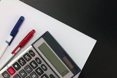大理企业财务整平机计算器、笔和白色白纸在黑背景 免版税库存照片