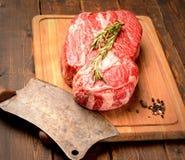 大理石小牛肉牛排用迷迭香和芳香香料,肉的一把刀子在木背景的一个切板 库存照片