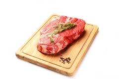 大理石未加工的小牛肉用迷迭香和芳香香料在一个切板在白色背景 免版税图库摄影