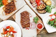 大理石牛肉和猪肉烤牛排  服务在一张土气桌上的一个木板 烧烤店菜单,系列 免版税库存图片