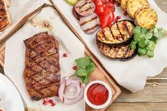 大理石牛肉烤牛排  服务在一张土气桌上的一个木板 烧烤店菜单,一系列的照片 免版税库存照片