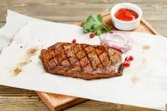 大理石牛肉牛排,烤 服务在一张土气桌上的一个木板 烧烤店菜单,一系列的照片 免版税库存图片