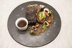 从大理石牛肉肉的Ribeye牛排与菜和烤肉汁 服务在黑石头板材  图库摄影