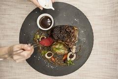 从大理石牛肉肉的Ribeye牛排与菜和烤肉汁 服务在黑石头板材  库存照片