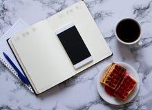 大理石背景、咖啡、奶蛋烘饼和智能手机的两位计划者 免版税库存图片