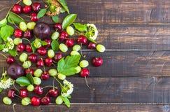 大甜水多的樱桃、李子和葡萄、叶子和花在木背景 免版税库存图片