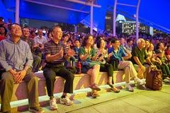 大男孩音乐会人群女孩晚上看见坐阶段 图库摄影