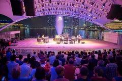 大男孩音乐会人群女孩晚上看见坐阶段 免版税图库摄影