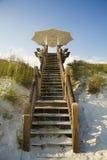 大白色伞海滩前面木板走道 图库摄影