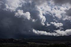 大白色和灰色积云隐约地出现在城市在山的基地 库存照片