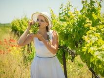 大白色帽子的妇女吃在领域的绿色葡萄 免版税图库摄影