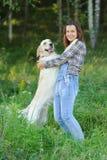 大白色狗在它的所有者上肩膀把爪子放  免版税库存照片
