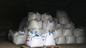 大白色袋子在仓库里-产品和肥料 免版税库存照片