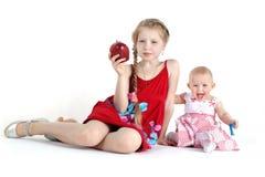 大的姐妹8年和11个月用苹果 免版税图库摄影