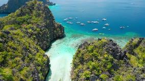 大盐水湖,El Nido,巴拉旺岛,菲律宾 在石灰石峭壁之间的寄生虫空中飞行在入口上浅水区  股票视频