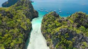 大盐水湖,El Nido,巴拉旺岛,菲律宾 在石灰石峭壁之间的寄生虫空中飞行在入口的浅水区上 股票视频