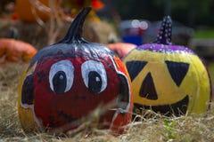 大眼睛红色南瓜和微笑的黄色南瓜 免版税图库摄影