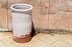 大石头,黏土老古老葡萄酒黄色雕刻了重的圆柱形白色水罐,有样式的一个花瓶在反对s的一个石地板上 图库摄影