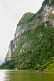 大石灰石峭壁和竹子小船 免版税图库摄影