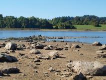 大石头、池塘、森林和草甸在背景中 库存图片