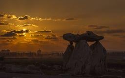 大石头剪影在橙色sunset& x27的; s cloudscape背景 免版税图库摄影