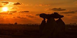 大石头剪影在橙色sunset& x27的; s cloudscape背景 免版税库存图片