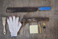 大砍刀和手套、锤子和一个老笔记本 库存照片