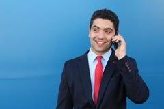 大笑在电话的一个笑话的商人 免版税库存图片