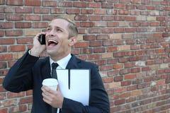 大笑在电话的一个笑话的商人 免版税库存照片