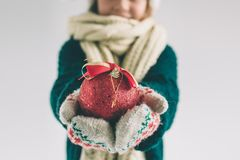 大红色圣诞节球在女孩的手上 孩子在毛线衣、圣诞节帽子和围巾演播室射击打扮 库存图片