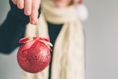 大红色圣诞节球在妇女的手上 女孩在毛线衣、圣诞节帽子和围巾演播室射击打扮 库存照片