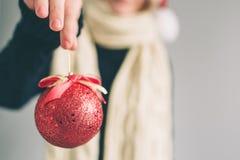 大红色圣诞节球在妇女的手上 女孩在毛线衣、圣诞节帽子和围巾演播室射击打扮 免版税库存图片