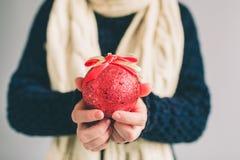 大红色圣诞节球在妇女的手上 女孩在毛线衣、圣诞节帽子和围巾演播室射击打扮 免版税库存照片