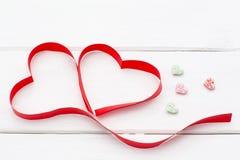 大红色心脏丝带和一些小白色木背景 库存图片