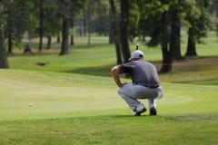 大约正确的线在绿色蹲的9月未知的高尔夫球运动员单独集中寻求的都灵意大利 图库摄影