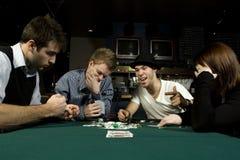 大约演奏啤牌表的四个朋友 免版税库存图片