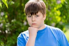 大约12年的男孩画象在公园 免版税库存图片