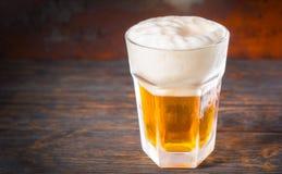 大结冰的玻璃用低度黄啤酒和泡沫一个大头在o的 图库摄影