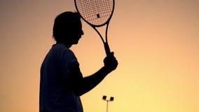 大网球 运动员在橙色日落的背景在他的肩膀上站立并且拿着球拍,然后把它放 股票录像