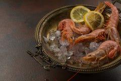 大老虎虾用柠檬和冰块在古老板材在黑暗的石背景 在开胃海鲜快餐的看法 免版税图库摄影